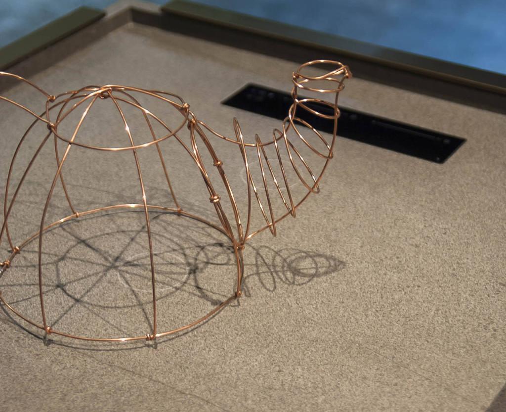 Una scultura in metallo riproduce il bollitore per indicare sul piano di Ariostea proposta da Binova dove è possibile cucinare