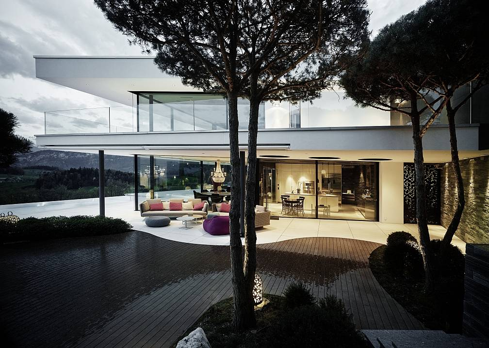 Dalle pareti vetrate della villa si intravede la cucina, sulla destra. Fuori, il patio arredato e la piscina