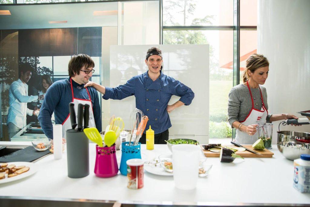 Lo chef Maurizio Rosazza Prin ha coinvolto due degli invitati nello show cooking realizzato durante l'incontro con i propri clienti