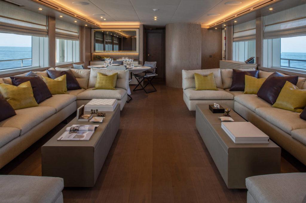 Il living coperto del Main Deck, con divani laterali e, sul fondo, area pranzo e accesso alla cucina